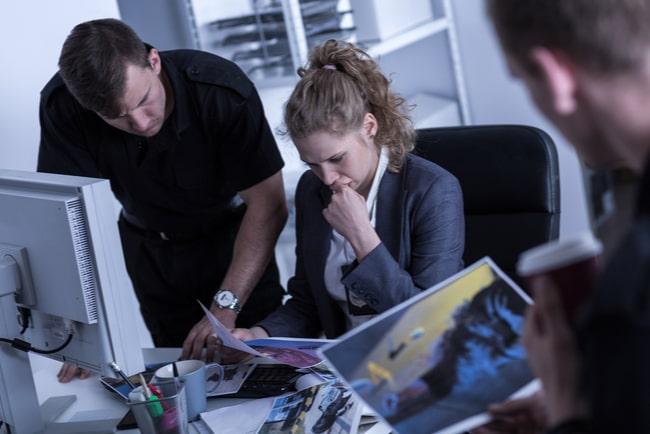 En kvinnlig polis och två manliga poliser tittar på bilder av ett brott