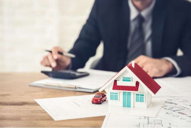 man som räknar på sin hushållsekonomi med ett miniatyrhus och leksaksbil på bordet
