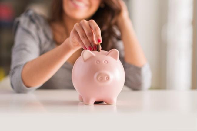 leende kvinna lägger mynt i en spargris
