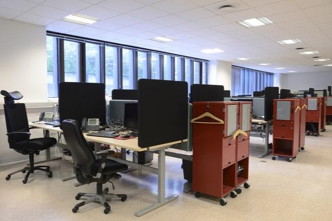 Kontorslandskap med skrivbord och stolar, inga människor.