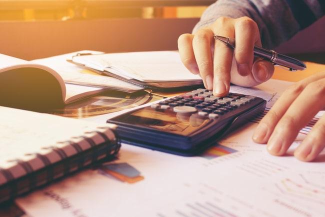 Person som sitter och räknar på miniräknare och gör en budget