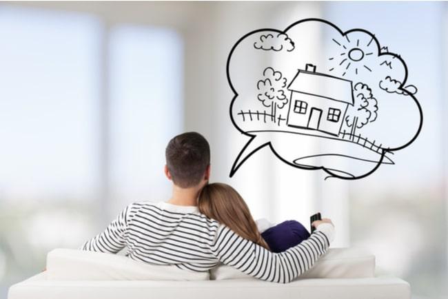 Ung kille och tjej sitter i soffa och drömmer om att köpa hus