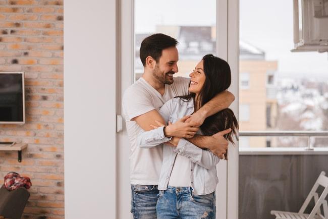 Ung man och kvinna är glada och kramas i deras nya lägenhet.