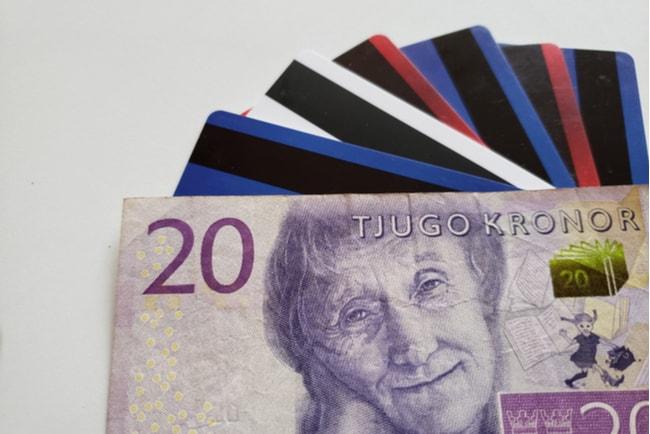 En tjugokronorssedel med sex bakåtvända kreditkort bakom sedeln