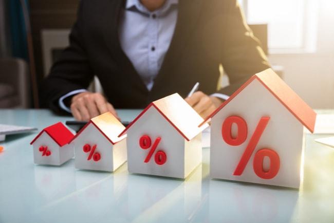 Fyra husmodeller som har ett procenttecken framför sig och som ökar i storlek och en man som sitter och skriver i bakgrunden.