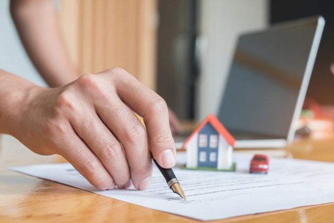 Man som skriver under ett dokument med miniatyrmodell av ett hus och en röd bil och en laptop i bakgrunden.