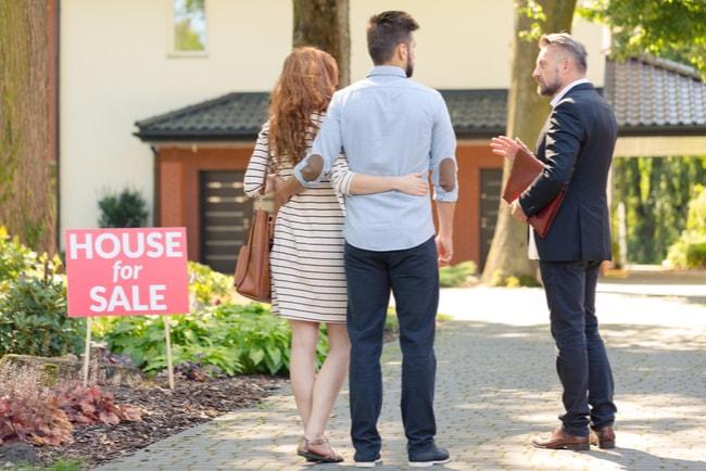 Ung man och kvinna som går på visning av bostad