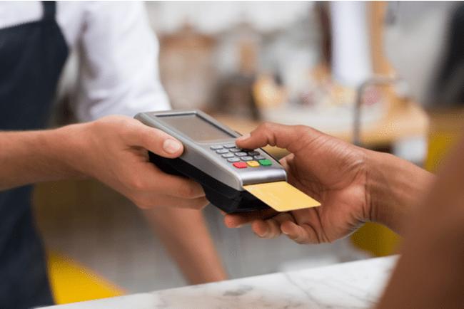 Hand som håller i kortterminal och handen på en kund som betalar med sitt kort i kortterminalen.