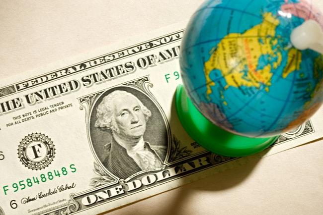 Jordglob i miniatyr som står på en dollar.