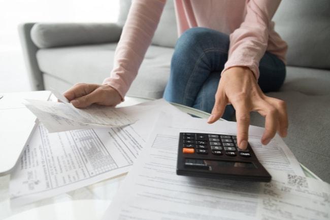 Kvinna sitter i soffa med miniräknare och räkningar på ett soffbord framför sig.
