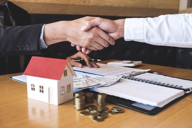 Två personer skakar hand över ett skrivbord angående ett avtal gällande bolån. På skrivbordet står ett miniatyrhus, en uppslagen kalender, dokument och pengar i olika valörer.