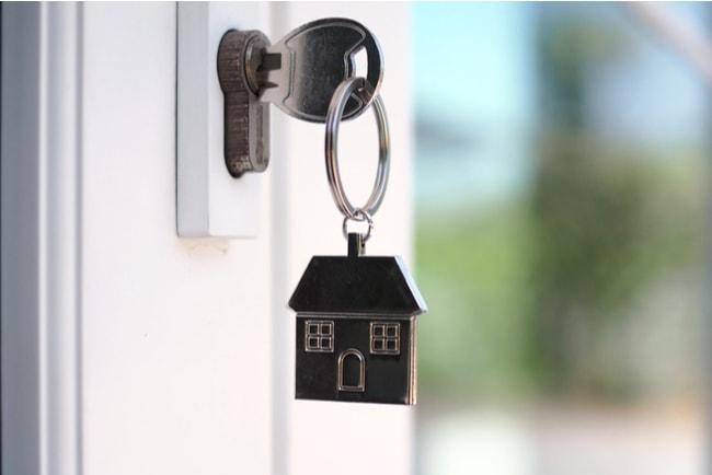 Husnyckel i en dörr som låser upp dörren.