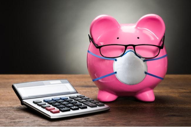 Rosa spargris med munskydd och glasögon står på ett bord med en miniräknare bredvid