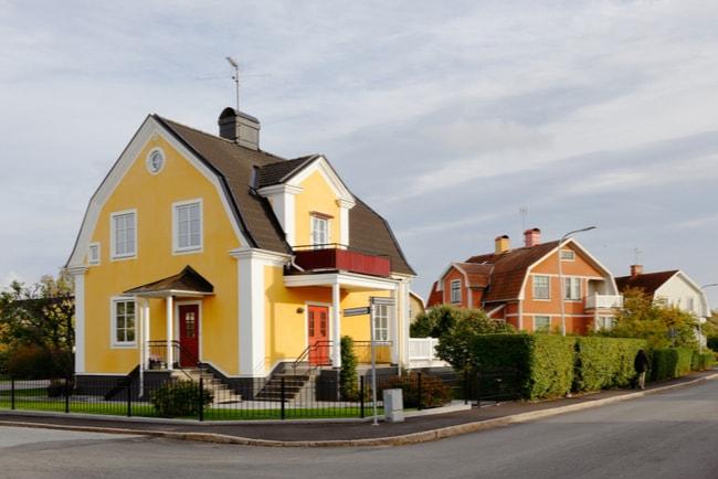 Gata i en förort i Sverige med en gul villa i ett gathörn och ett ljusrött flerfamiljshus.