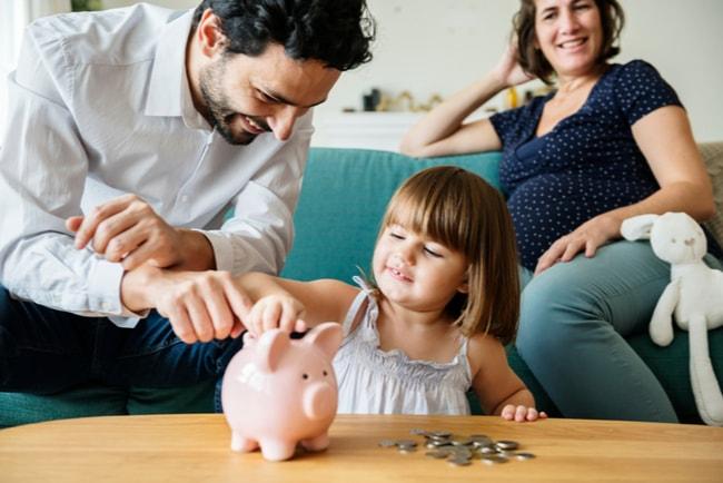 liten flicka stoppar mynt i spargris med hjälp av föräldrar