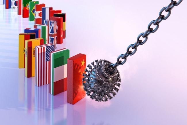 Coronaviruset i en pendel som åker mot dominobrickor med olika flaggor