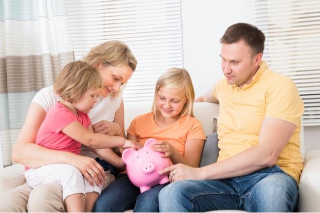 Familj med två vuxna och två små barn, sitter i en soffa tillsammans och stoppar pengar i en rosa spargris.