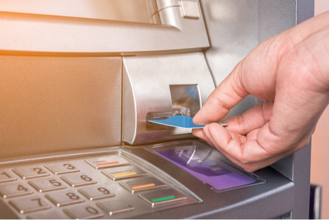 Närbild av hand som sticker in ett kort i en bankomat