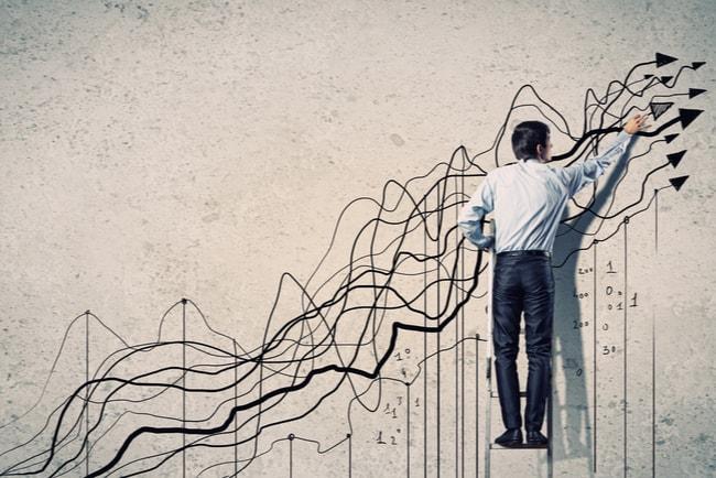 En man står på en stege vid en vägg och ritar grafik på väggen med pilar som pekar uppåt