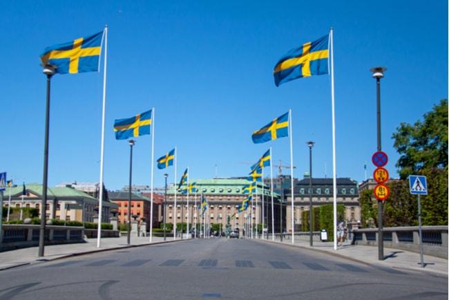 Norrbron i Stockholm kantad med hissade svenska flaggor