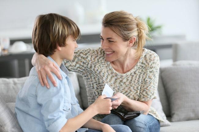 glad mamma ger sedlar till sin son