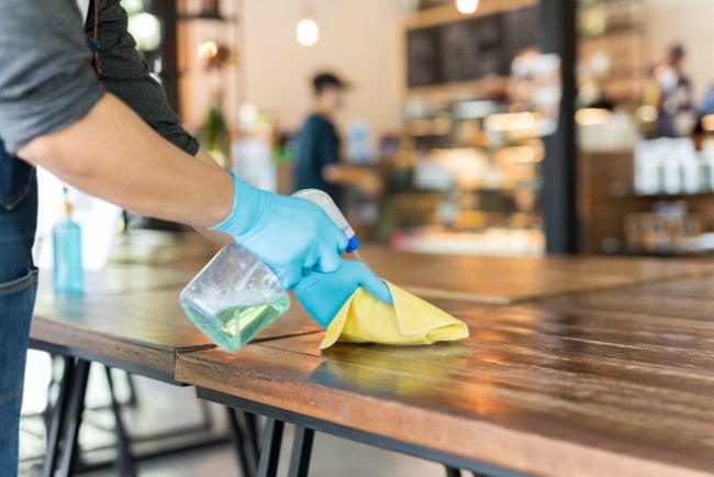 händer med handskar sprayar och torkar bord på en restaurang