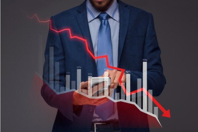 affärsman med diagram där ekonomin pekar neråt