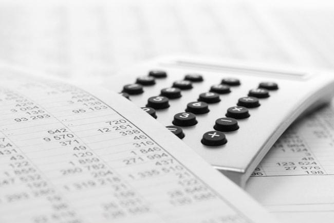 Papper med siffor som täcker en del av en vit miniräknare med svarta knappar