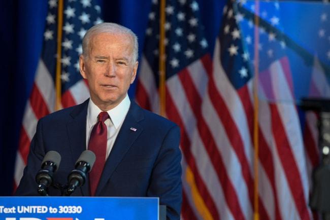 presidentkandidat joe biden håller tal med amerikanska flaggor i bakgrunden