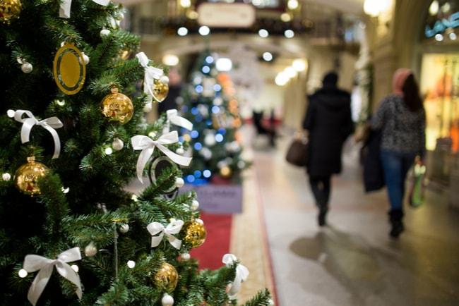 shoppingcentrum med julgran i förgrunden och strosande människor i bakgrunden