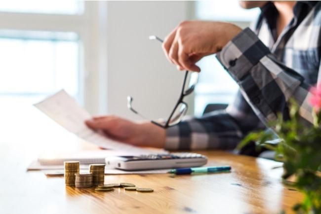orolig företagare läser finansiella papper vid skrivbord, med högar av mynt framför sig