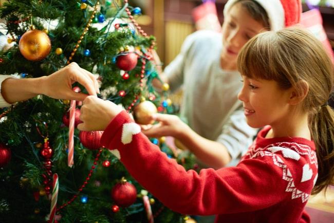 glad flicka och pojke klär julgran