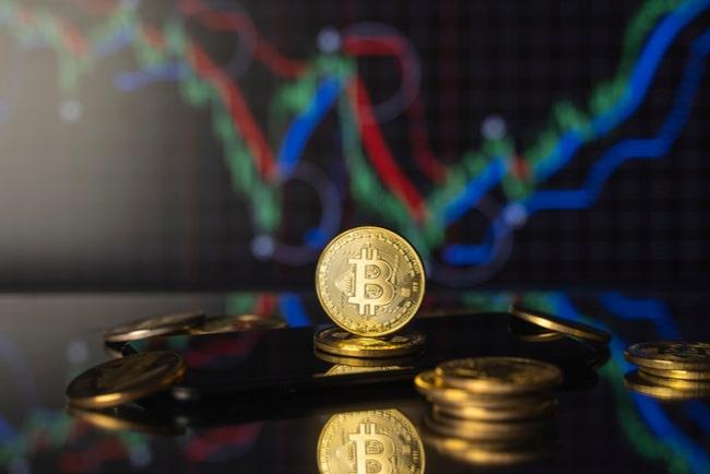 bitcoinmynt i guld med diragram i bakgrunden
