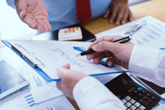 två företagare tittar på en clipboard med statistik
