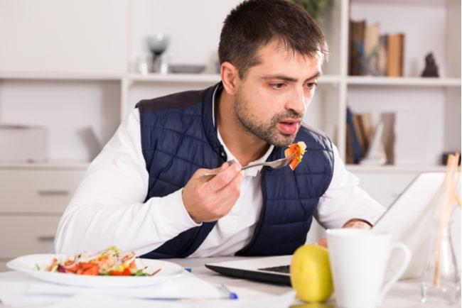 man äter lunch framför laptop i sitt hem