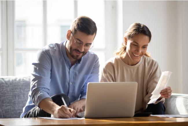 Man och kvinna sitter vid ett bord med laptop och papper och penna.