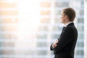 ung företagare tittar ut genom fönster på höghusbyggnader