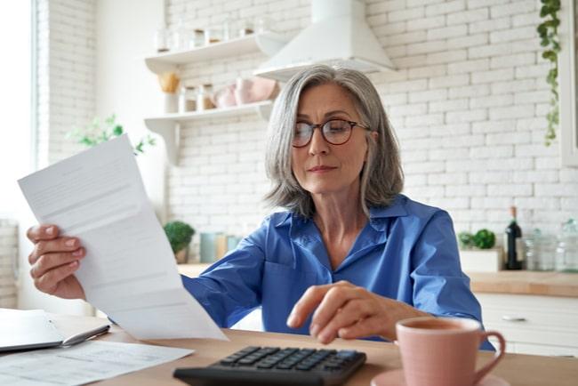 Äldre kvinna sitter vid ett bord och håller i ett papper samtidigt som hon knappar på en miniräknare.