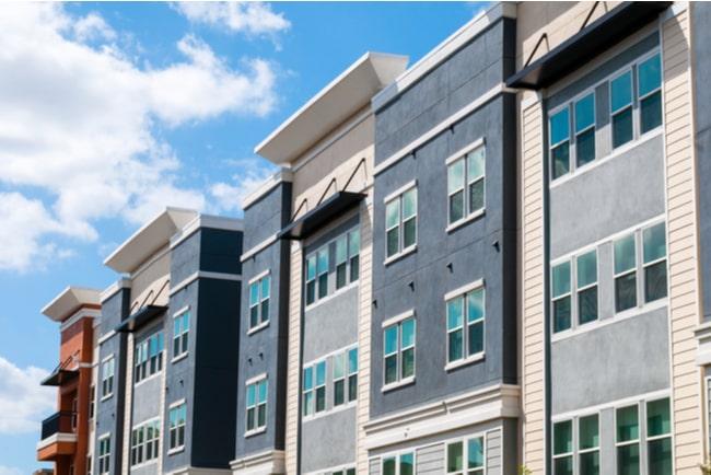 en rad med lägenhetshus mot blå himmel