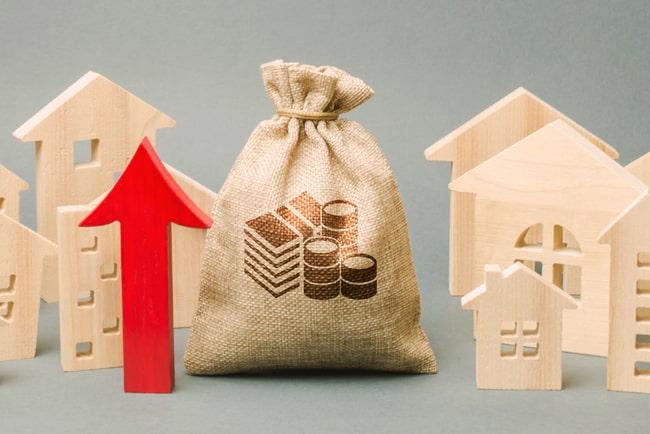 Små trämodeller av hus, säck med pengar och en röd pil som pekar uppåt.