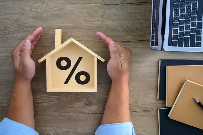 beskyddande händer runt miniatyrhus i trä med procenttecken