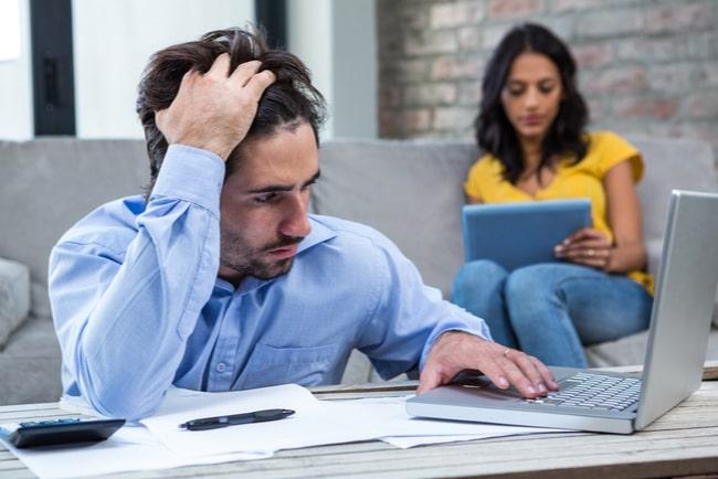 Ung man som ser oroad ut sitter vid ett bord med laptop och flera papper och miniräknare.