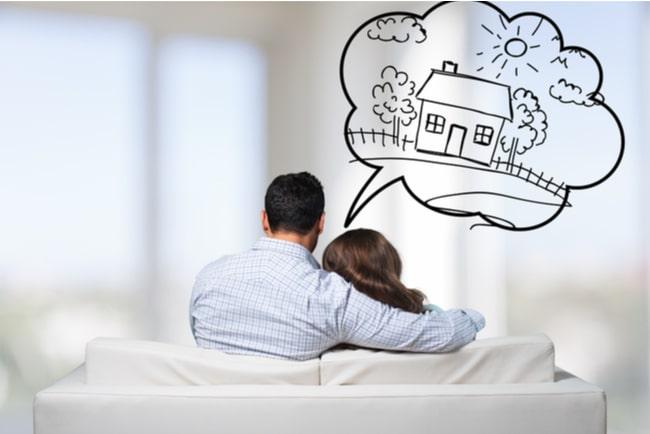 Ett par som sitter i en vit soffa och drömmer om en villa.