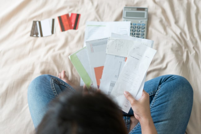 En person sett ovanifrån sitter och håller i flera räkningar med en miniräknare och fyra kreditkort framför sig.