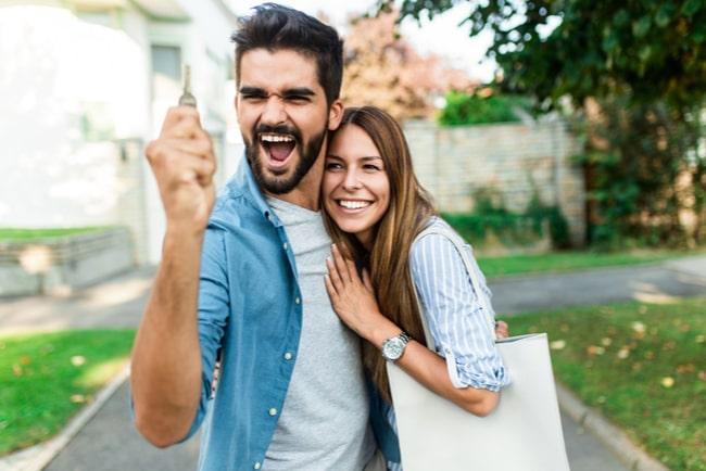lyckligt-ungt-par-där-mannen-håller-i-en nyckel