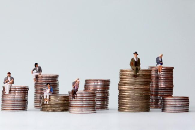 Miniatyrmänniskor som sitter eller står på flera olika myntpelare som ska visa klasskillnader i samhället.