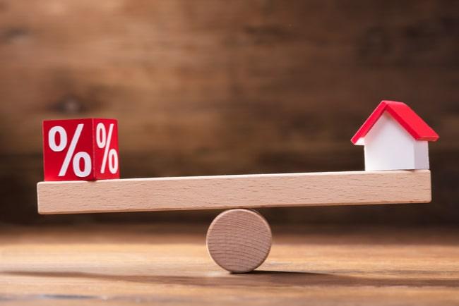 kub med procenttecken och miniatyrhus på balansbräda