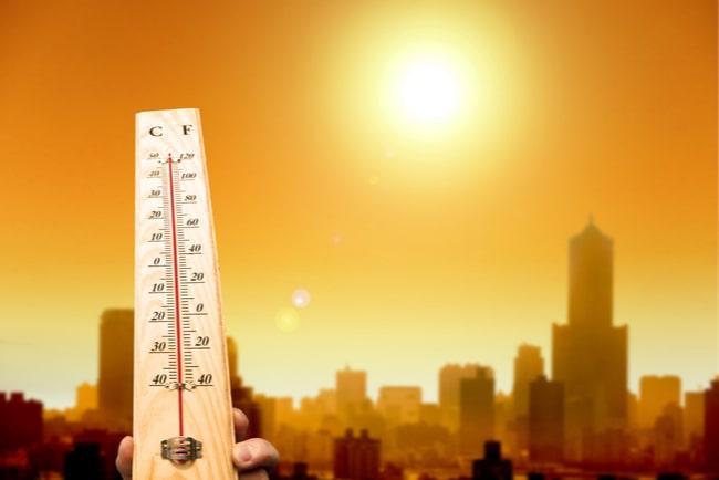 Termometer visar skyhöga temperaturer, med sol på gul himmel och konturerna av en stad i bakgrund.