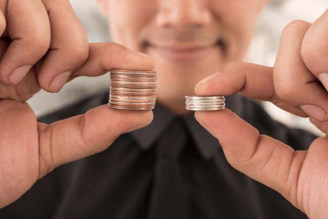 Man håller i två mynthögar mellan tumme och pekfinger. I vänster hand håller han en mindre hög med mynt och i höger hand en större hög med mynt.