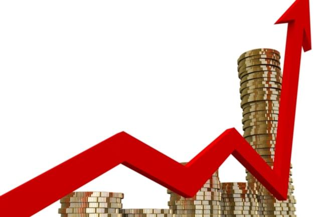 Mynt i olika staplar och en röd pil som pekar uppåt.